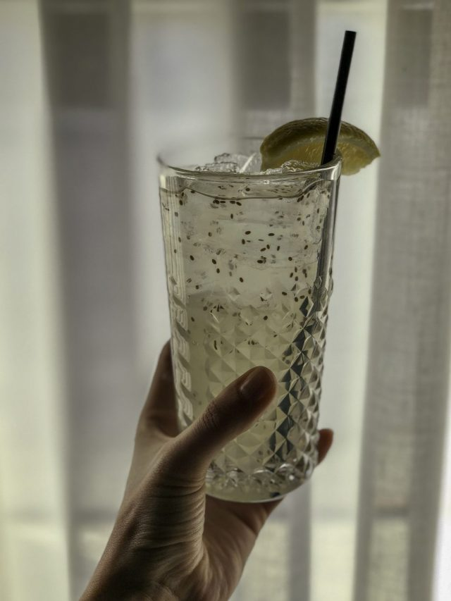 a hand holding a drink of lemonade with chia seeds in it