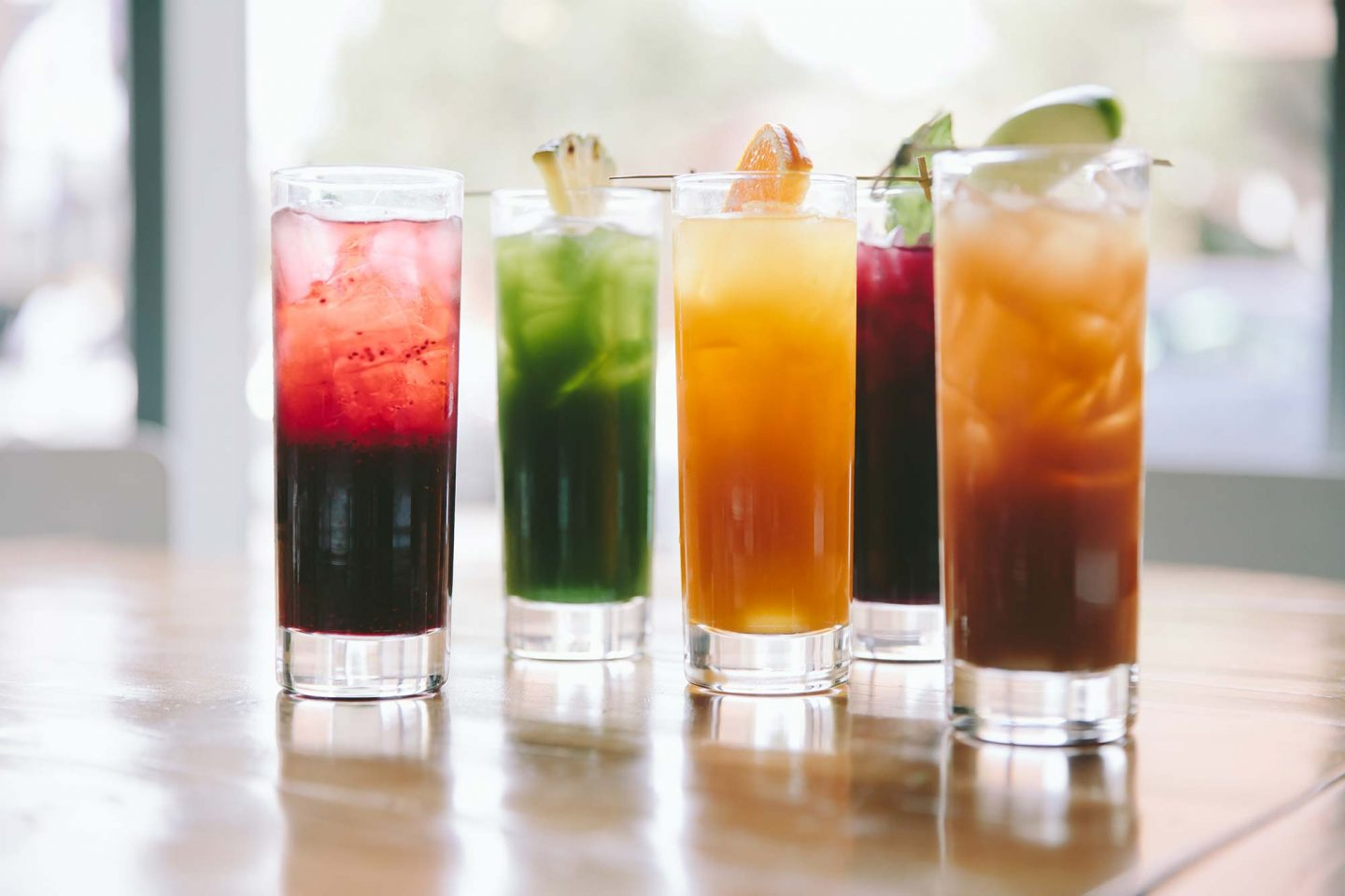 6 different colored juices sitting on a table in front of a window in tall, thin glasses
