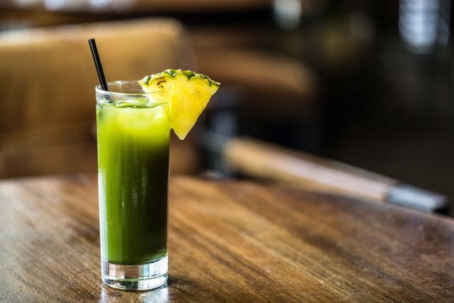 A green juice with a pineapple slice on the rim of the glass on a wooden table