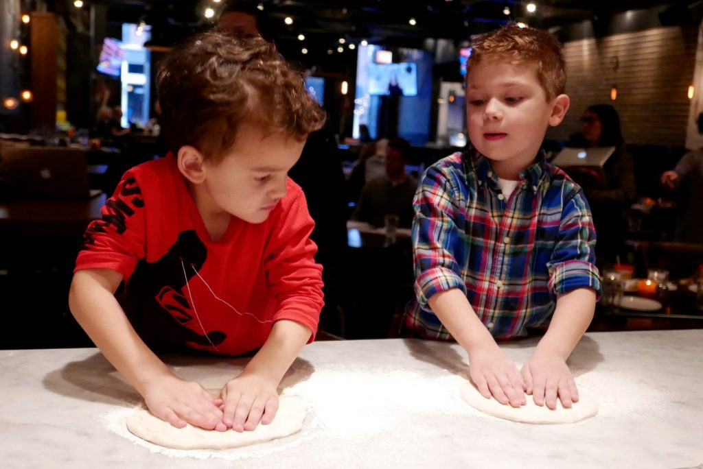 2 Young Boys rolling out pizza dough at the Stella Barra bar