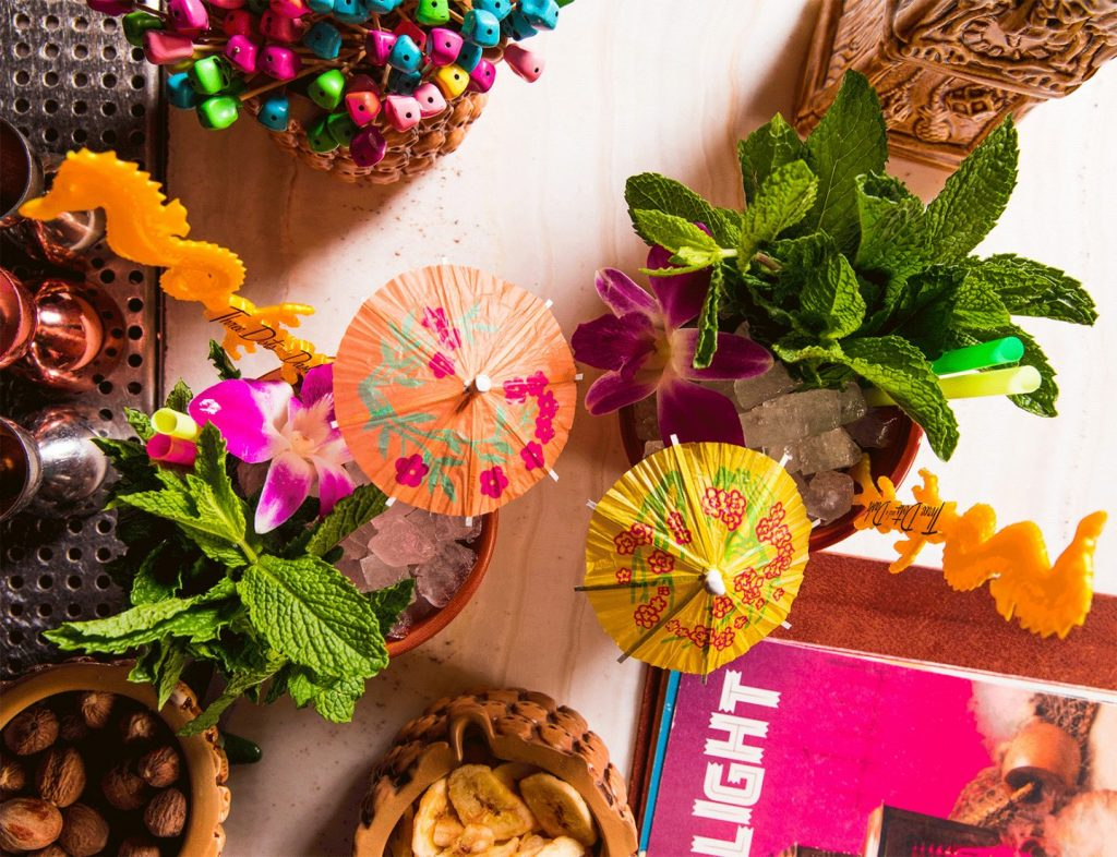 tiki drinks overhead with umbrellas and mint and nuts