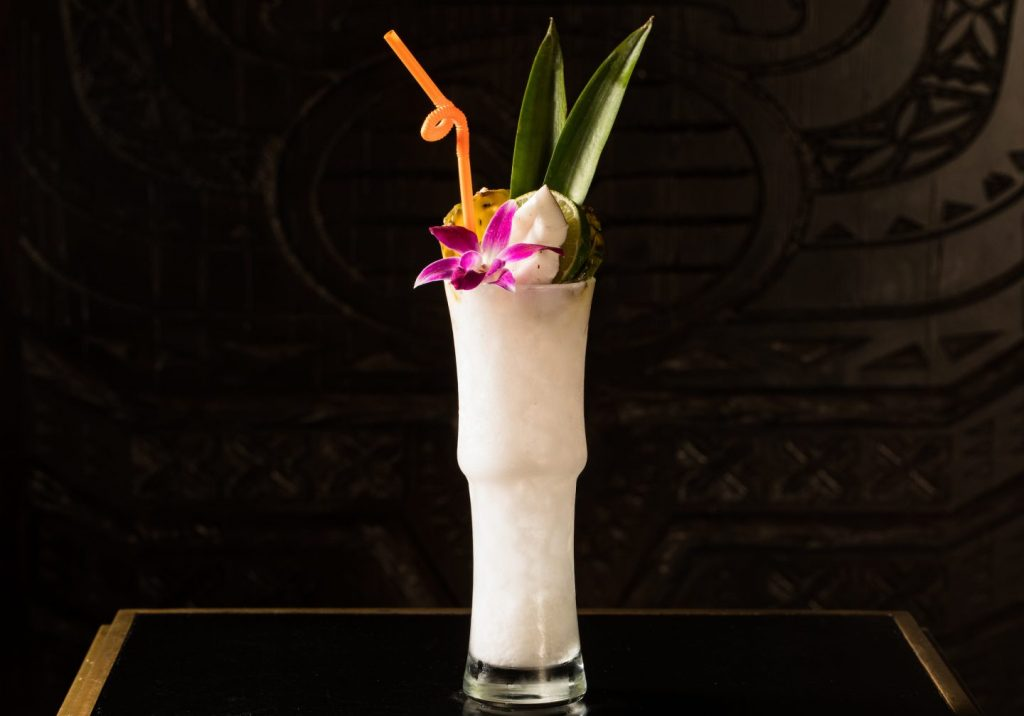 Tiki drink in a tall glass with pineapple leaves
