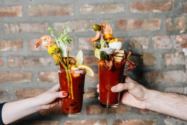 Two hands holding up their bloody marys cheersing each other in front of a brick wall
