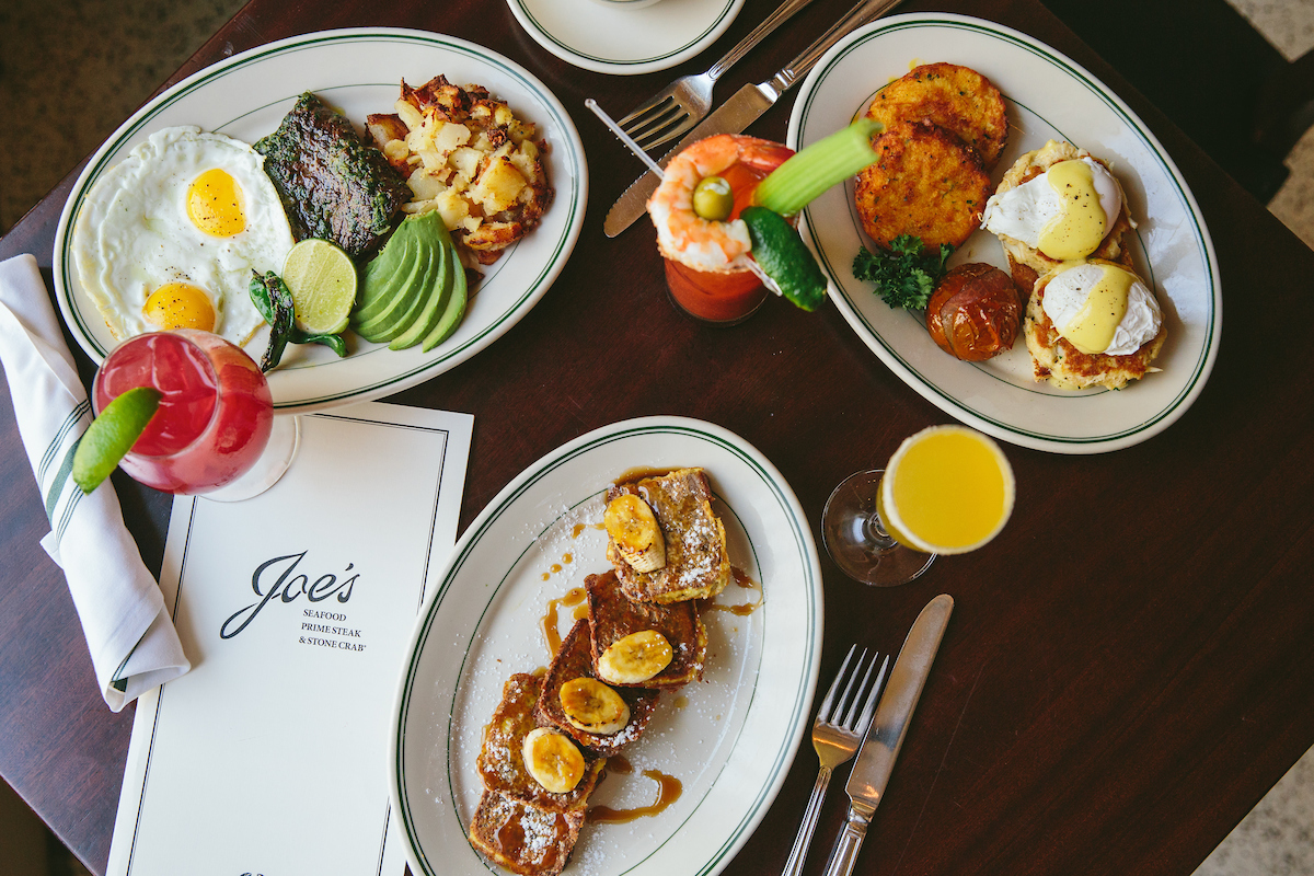 overhead photo of eggs with steak, bananas Foster french toast a benedict and cocktails at Joe's Seafood