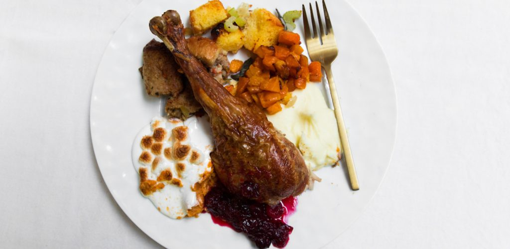 thanksgiving dinner with turkey, mashed potato, stuffing, sweet potatoes and cranberry