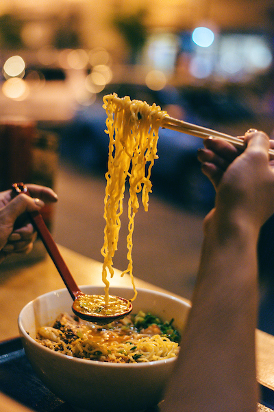 A ramen bowl with someone pulling up the noodles with chopsticks