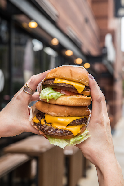2 M Burger's double-cheeseburgers being held on top of each other and held up outside the M Burger store