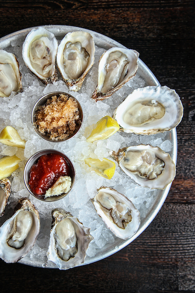 A tray of oysters on ice with sauce in the middle from Oyster Bah