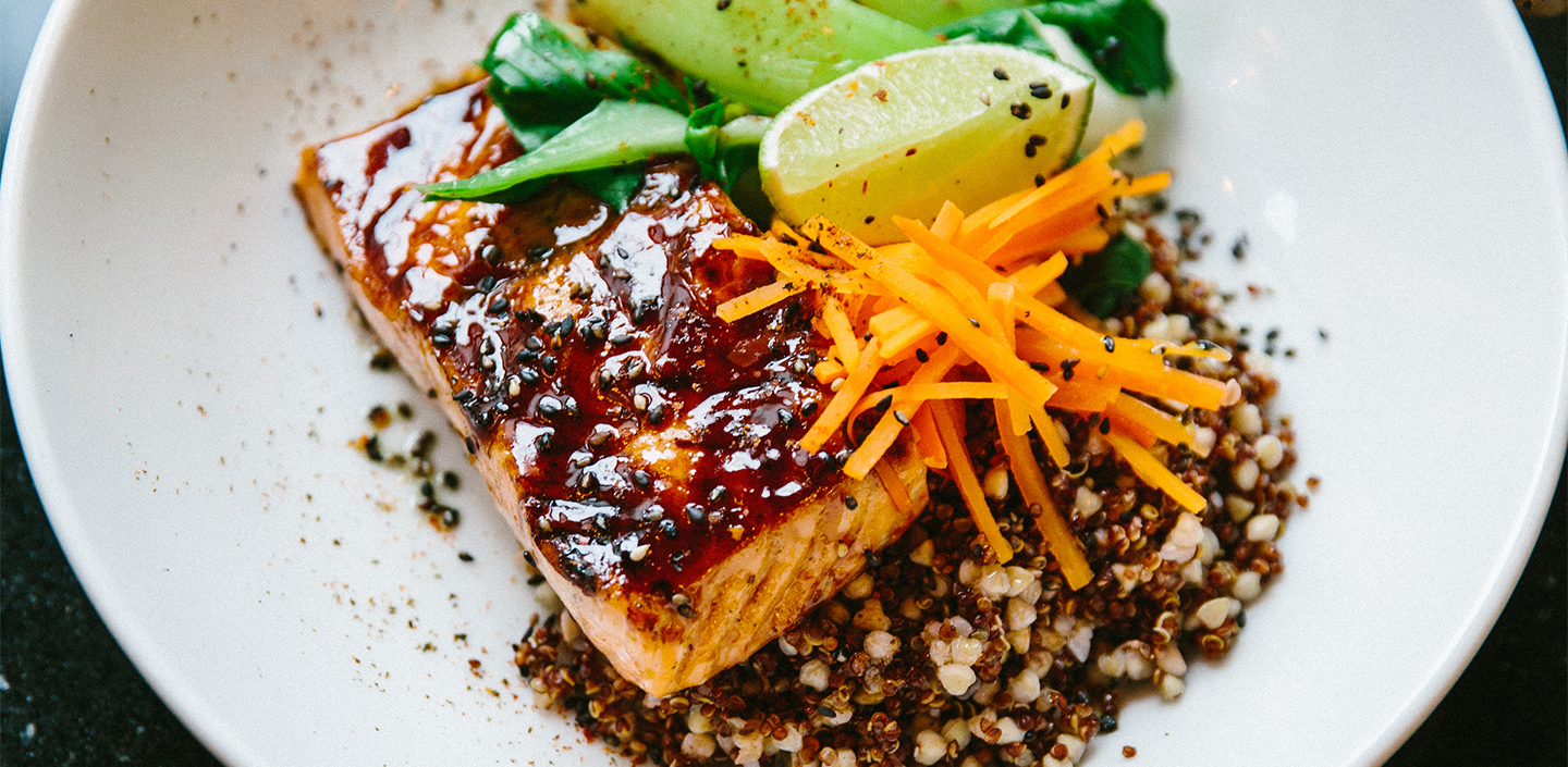 Salmon over quinoa with carrots and a lime wedge