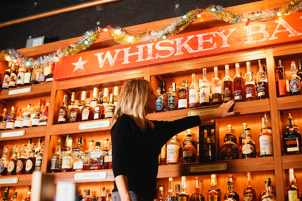 Diane, the beverage director, is standing in front of the whiskey wall in Bub City