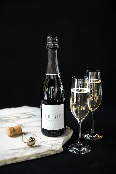 Giuliana Prosecco on a marble board with 2 champagne glasses