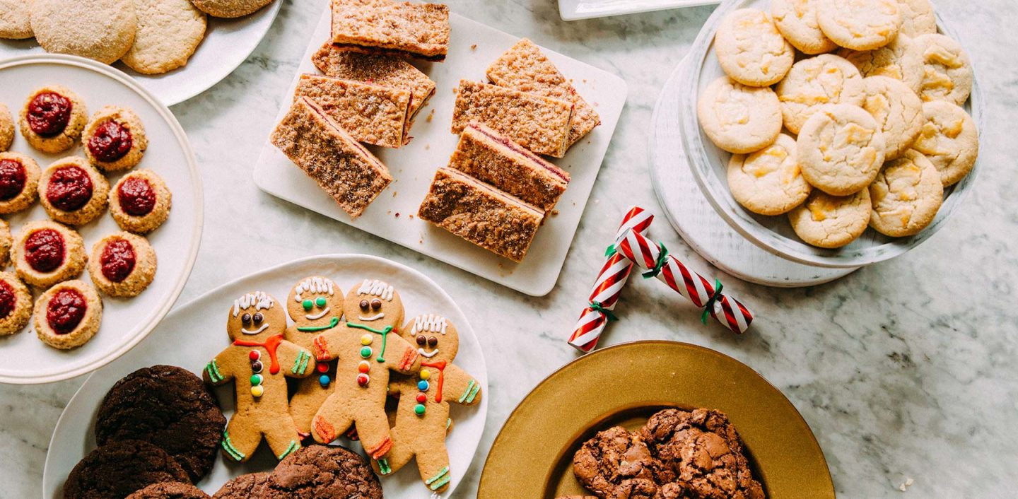 A white marble table covered in different holiday cookies from thumbprint cookies to gingerbread cookies