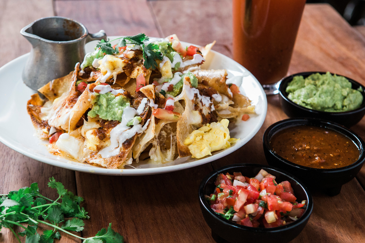 Breakfast Nachos at Hub 51, topped with scrambled eggs, guacamole, salsa, cheddar and oaxaca cheese