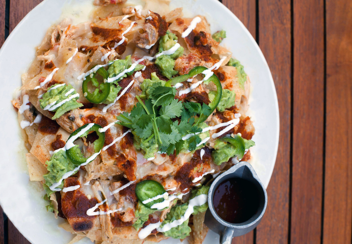A Hub 51 classic, the Pulled Chicken Nachos have guac, tomato salsa, cheddar and oaxaca cheeses