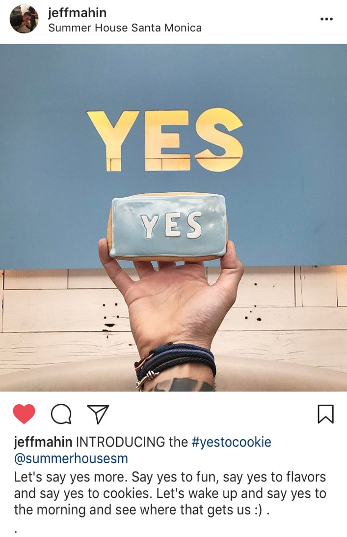 Screen shot from Jeff Mahin Instagram of Yes Cookie in front of a sign that says Yes