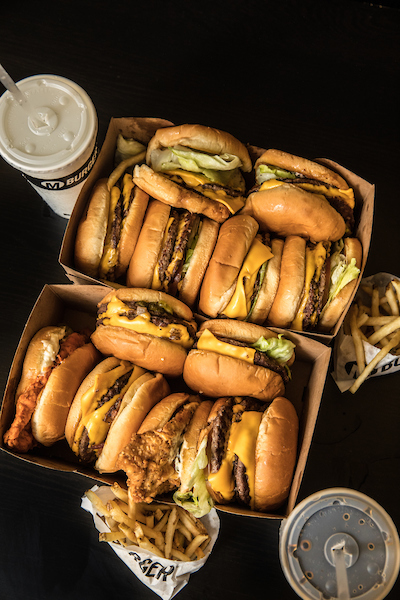 2 boxes of burgers with the burgers stacked on top of each other. A perfect catering of M Burger.