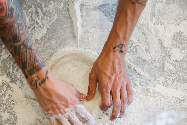 Hands, with arms tattoed, are working on pizza dough a flour surfaced