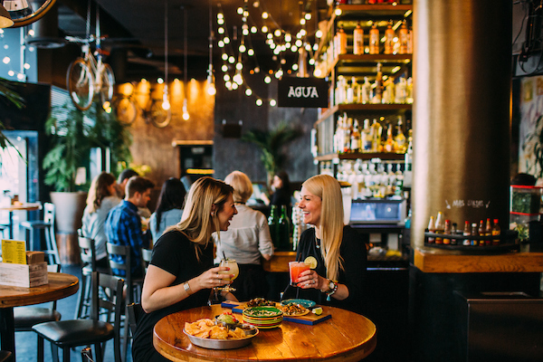 Tallboy's bar with 2 girls sitting at a table with drinks in their hands