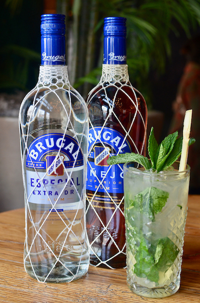 A glass of mojito with a straw next to 2 bottles of rum