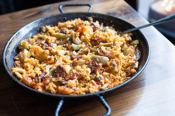 Paella from Cafe Ba-Ba-Reeba! in a pan on a table with a spoon in it