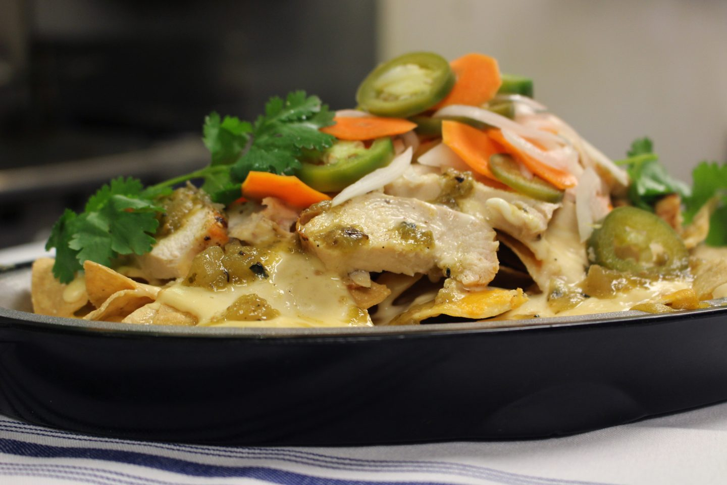 side view of the chicken nachos covered in beer cheese