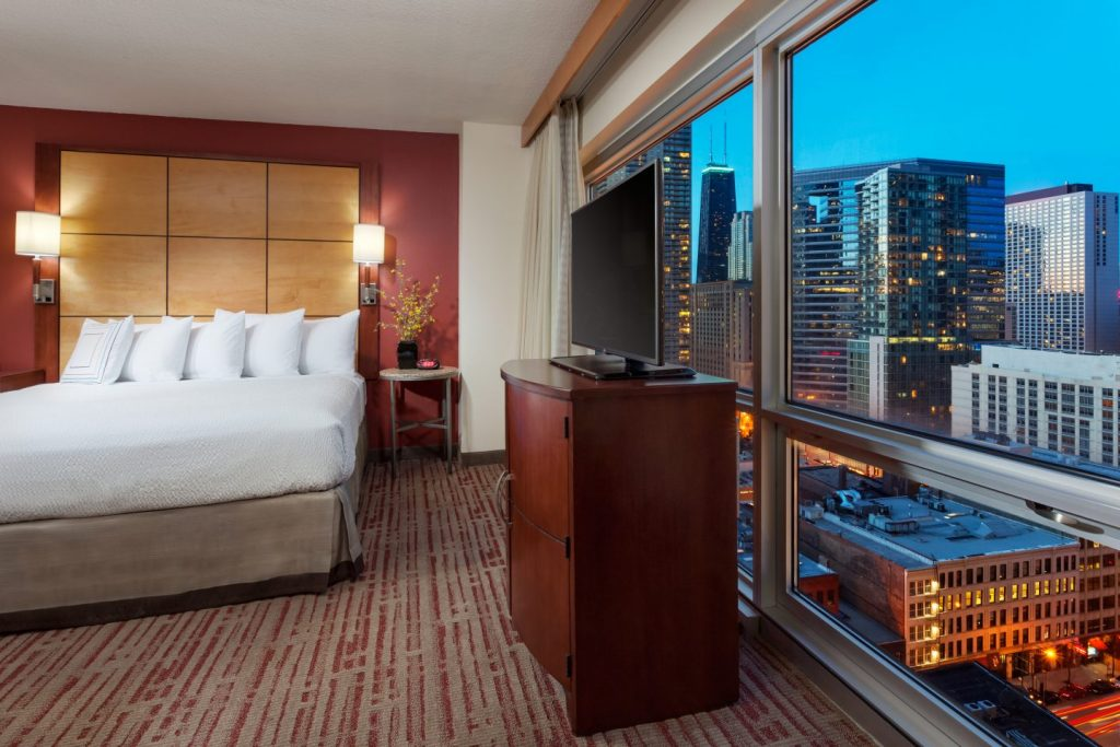 Bed in a hotel room with a view of Chicago