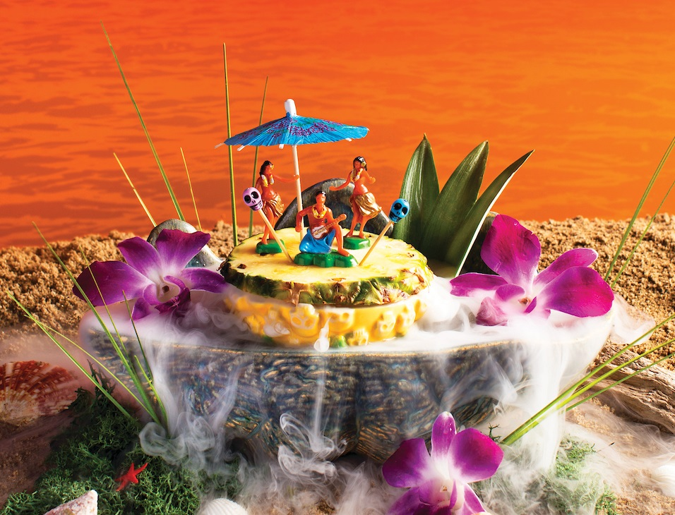 image of a cocktail with flower garnishes, pineapple slices and figurines of people on top