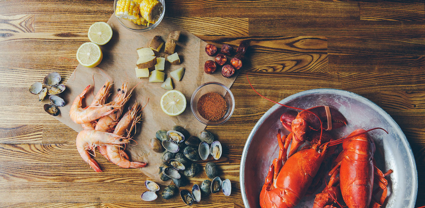 overhead shot of lobster, clams, shrimp, sausage and other ingredients