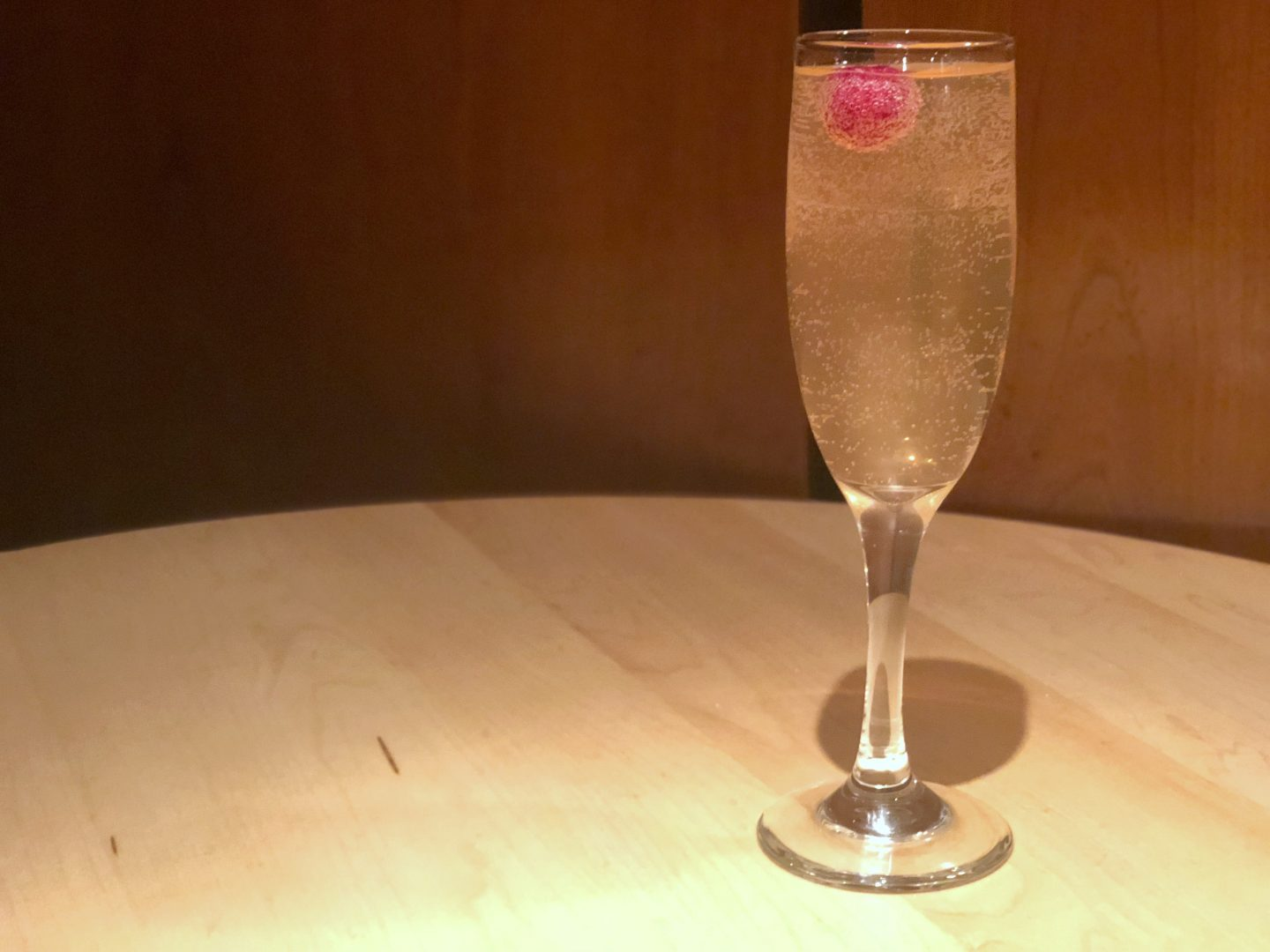 image of champagne in a flute with a raspberry
