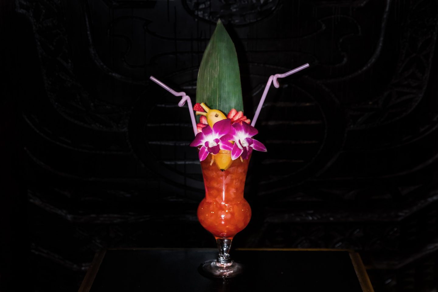 three dots and a dash cocktail with a banan dolphin and flowers as a garnish