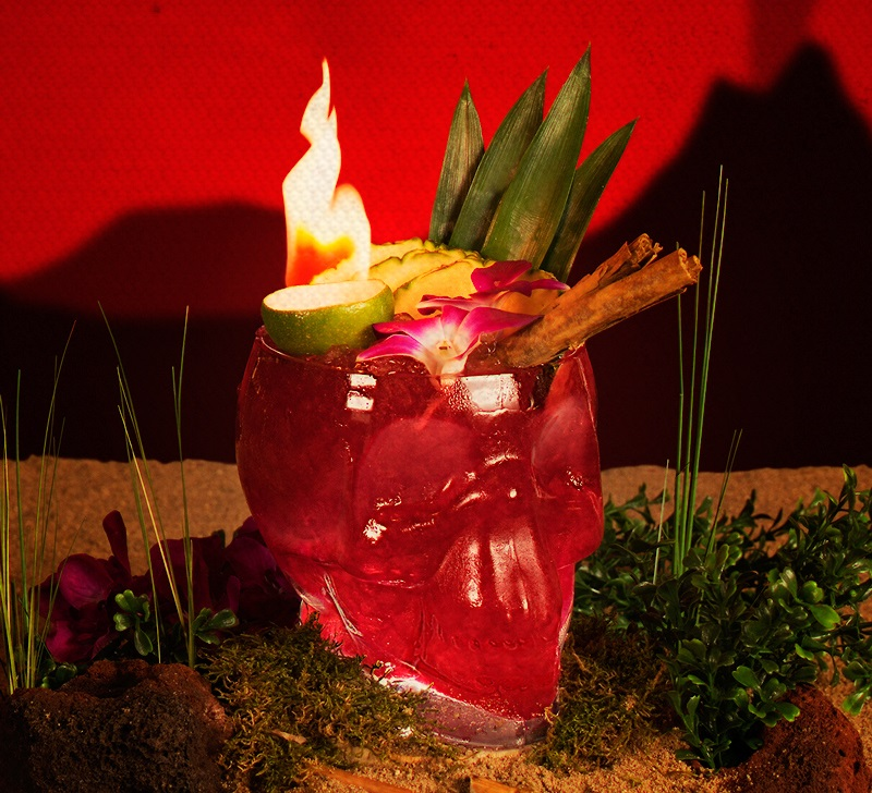 image of a red cocktail in a skull shaped glass that is on fire