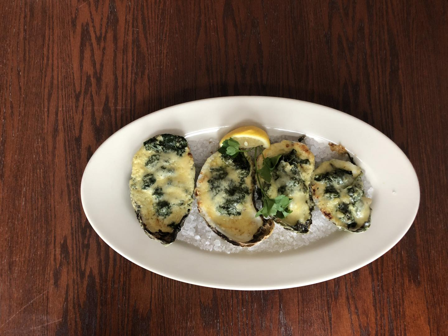 Four oysters rockefeller on a wood table at Shaw's Crab House