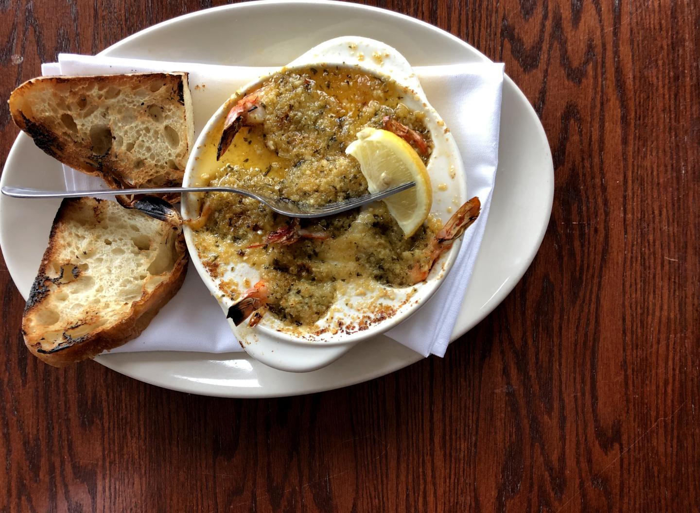 shrimp in butter in a escargot plate with grilled bread at shaw's crab house