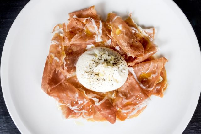 a plate filled with proscuitto and a ball of burratta on it