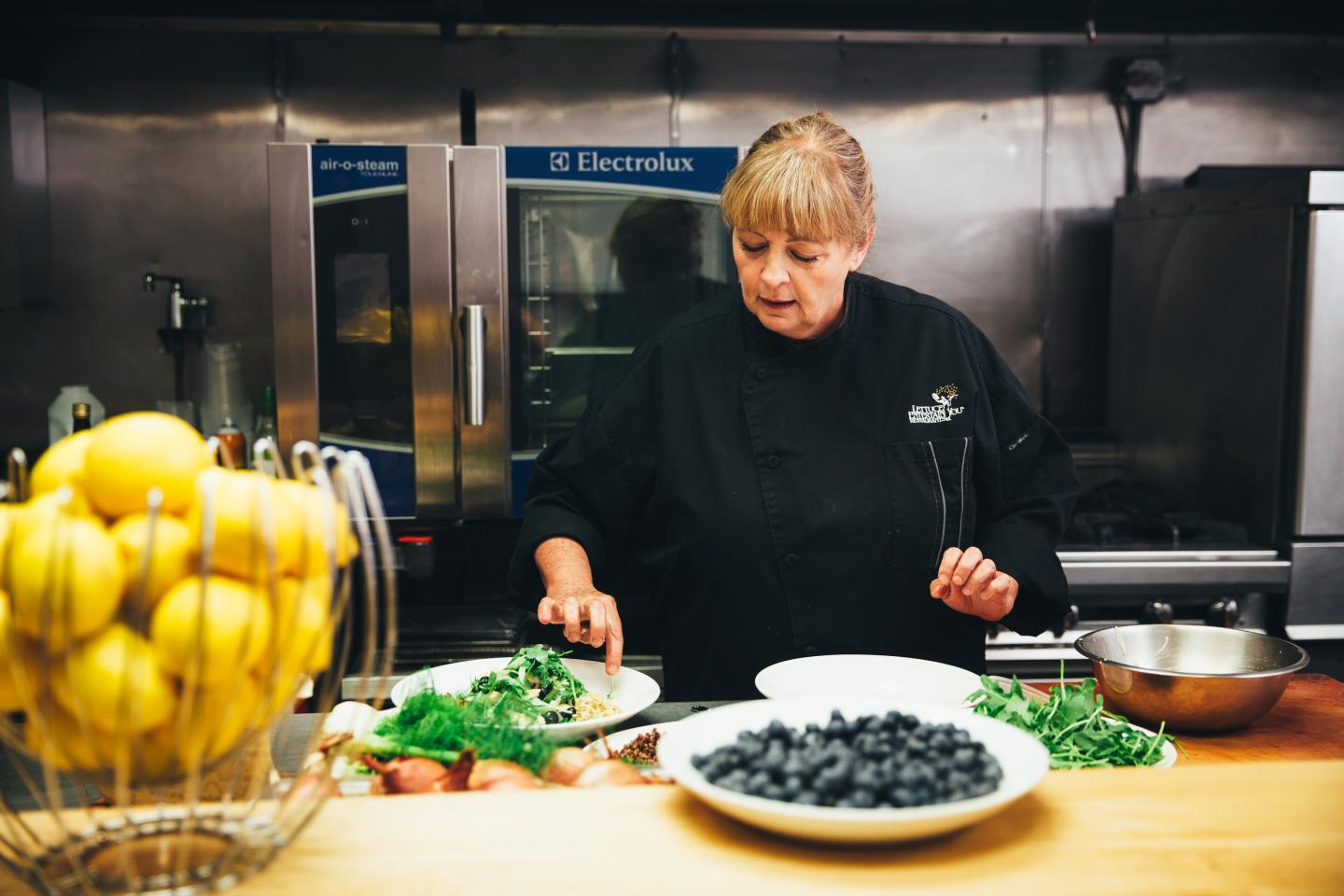 Chef Rita preparing a salad with arugula and blueberries