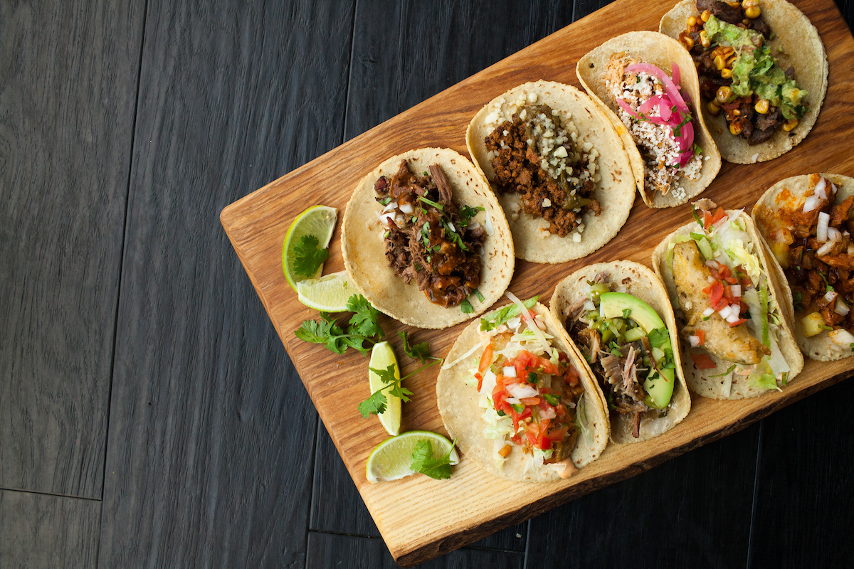 platter of tacos on a wooden board with lots of limes