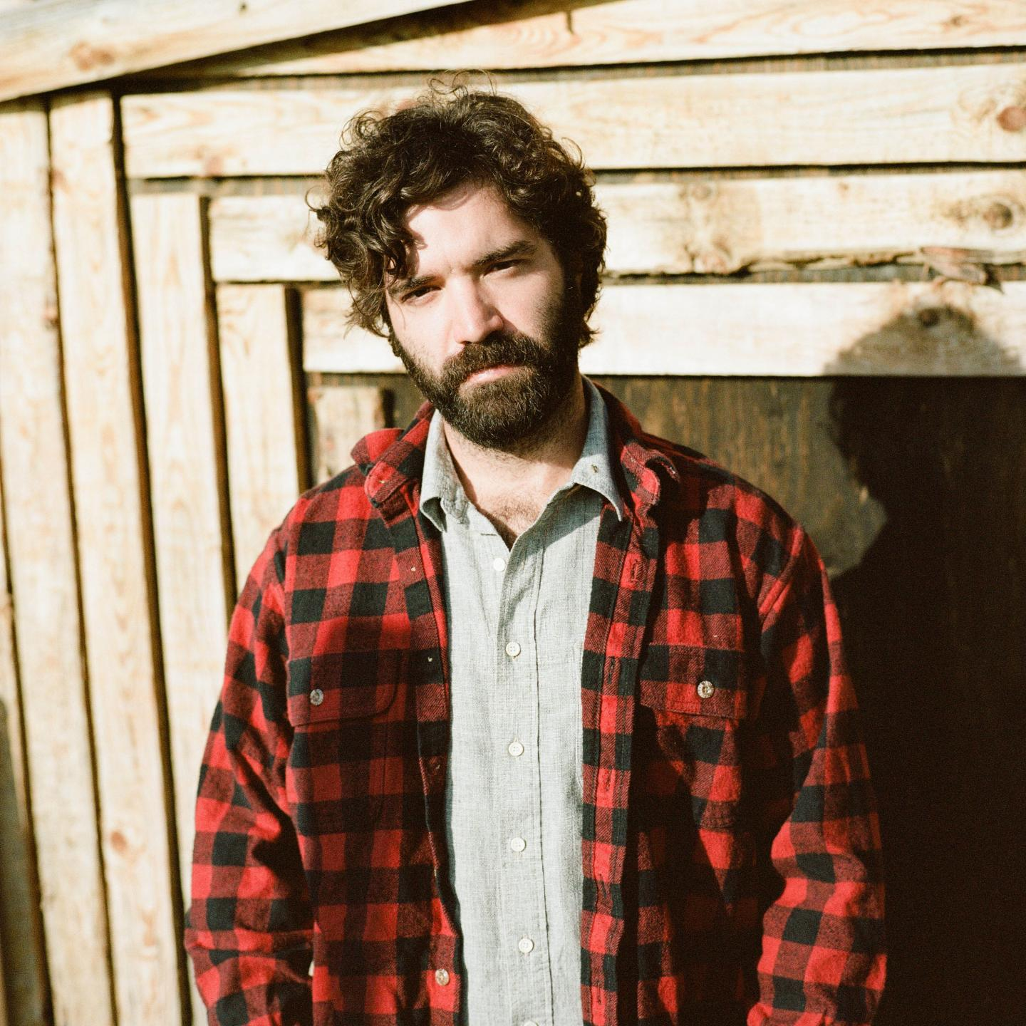 Andrew Duhon wearing a grey polo under a plaid button down in front of a wooden structure