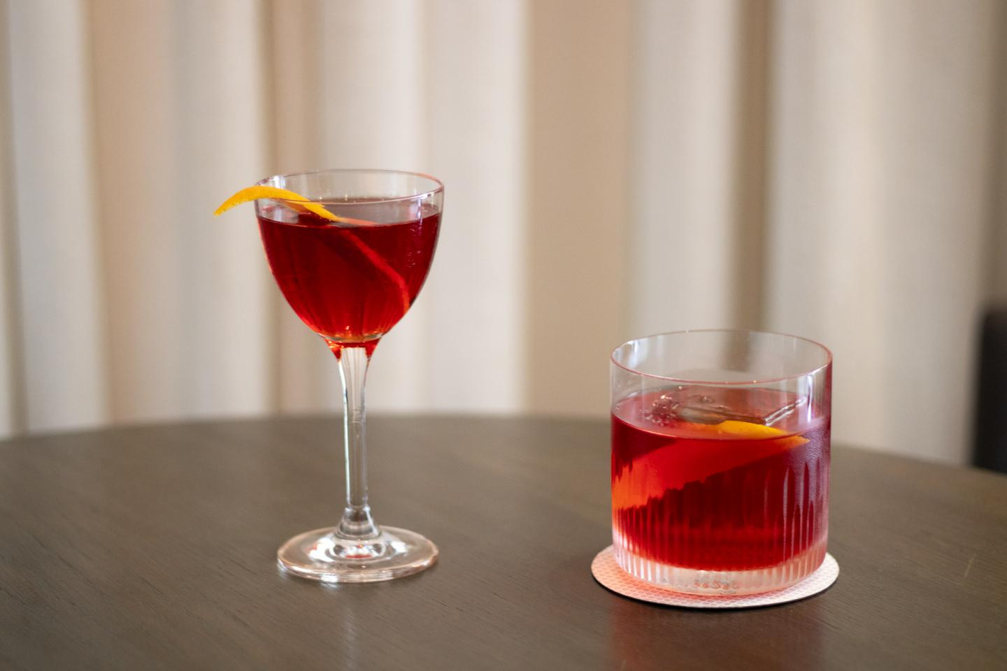 image of two negronis, one in a coupe, one in a rocks glass, at Booth One