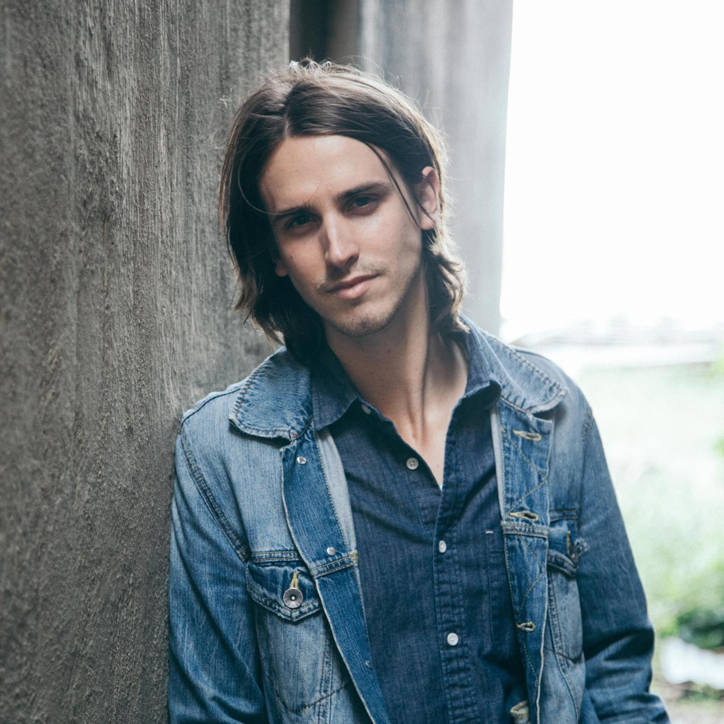 Troy Cartwright wearing a denim button down under a denim jacket leaning up against a wall