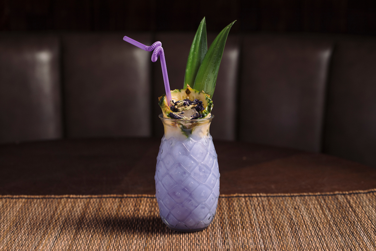 clear pineapple cup with purple drink and pineaplle garnish'
