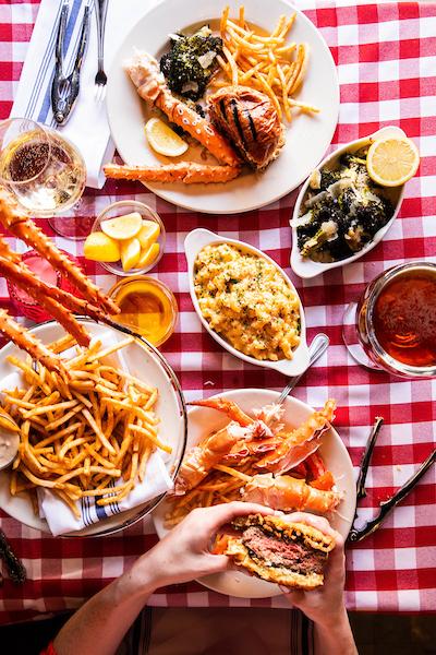 a platter of burgers and alaskan king crab