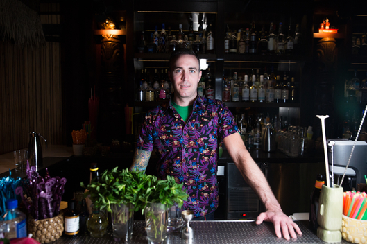 kevin beary at three dots wearing a purple shirt standing behind the bar