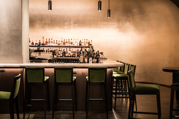 booth one bar with spirits on the back bar and green bar chairs