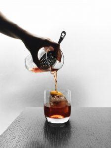 Pouring RPM Italian Negroni into glass