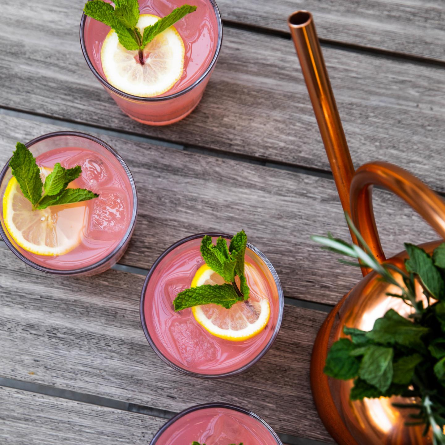 four pink cocktails garnished with lemon wheels and a copper watering can