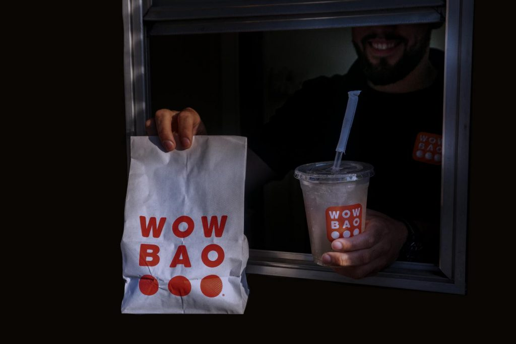 Wow Bao Late Night Window Man Holding Wow Bao Bag and Drink