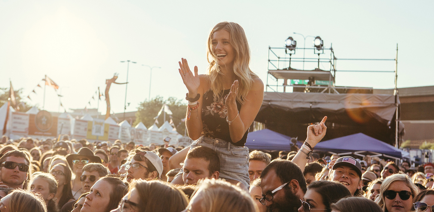 girl on shoulders in the crowd of the smokeout