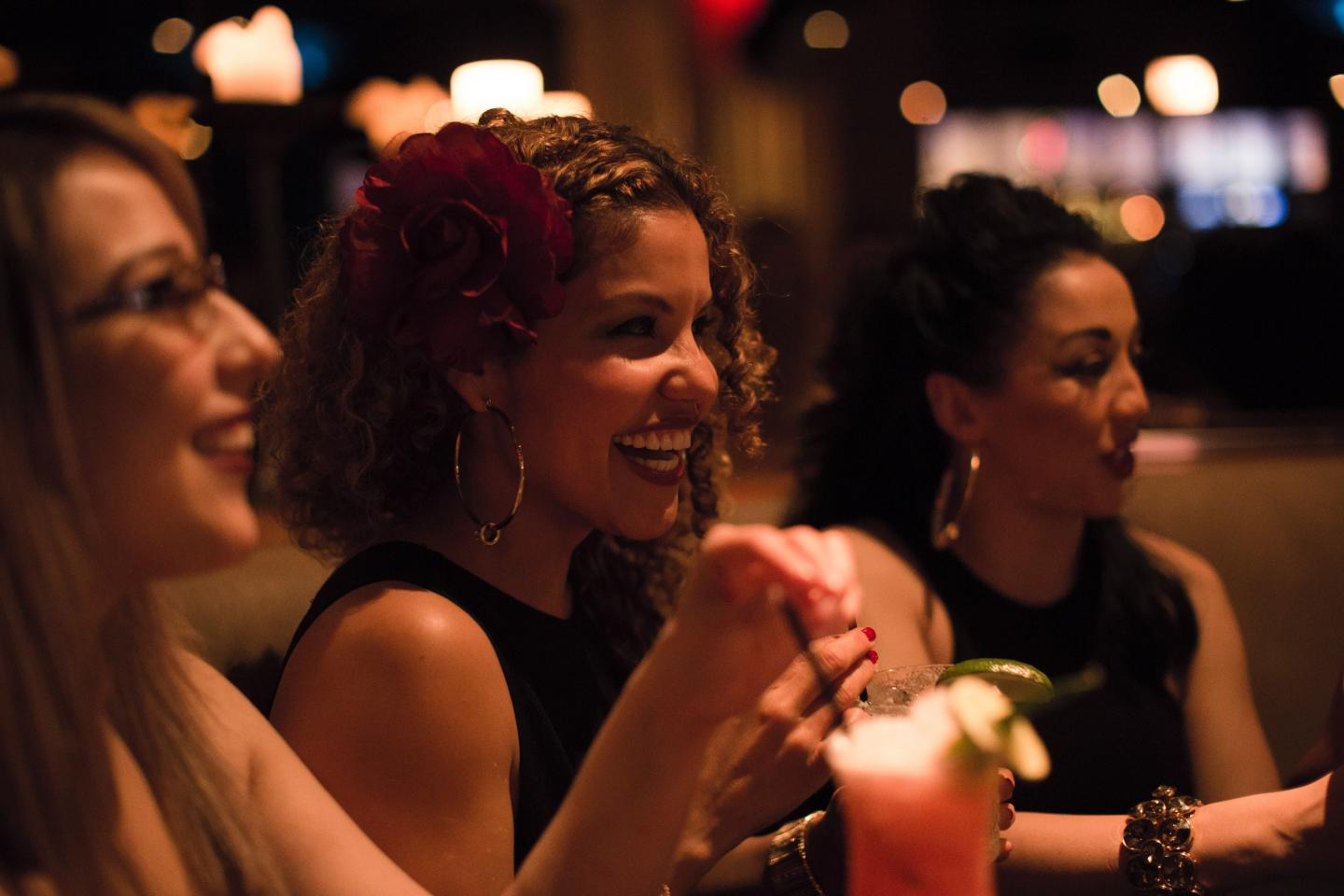 Girl with curly hair laughing with cocktail at Nacional 27