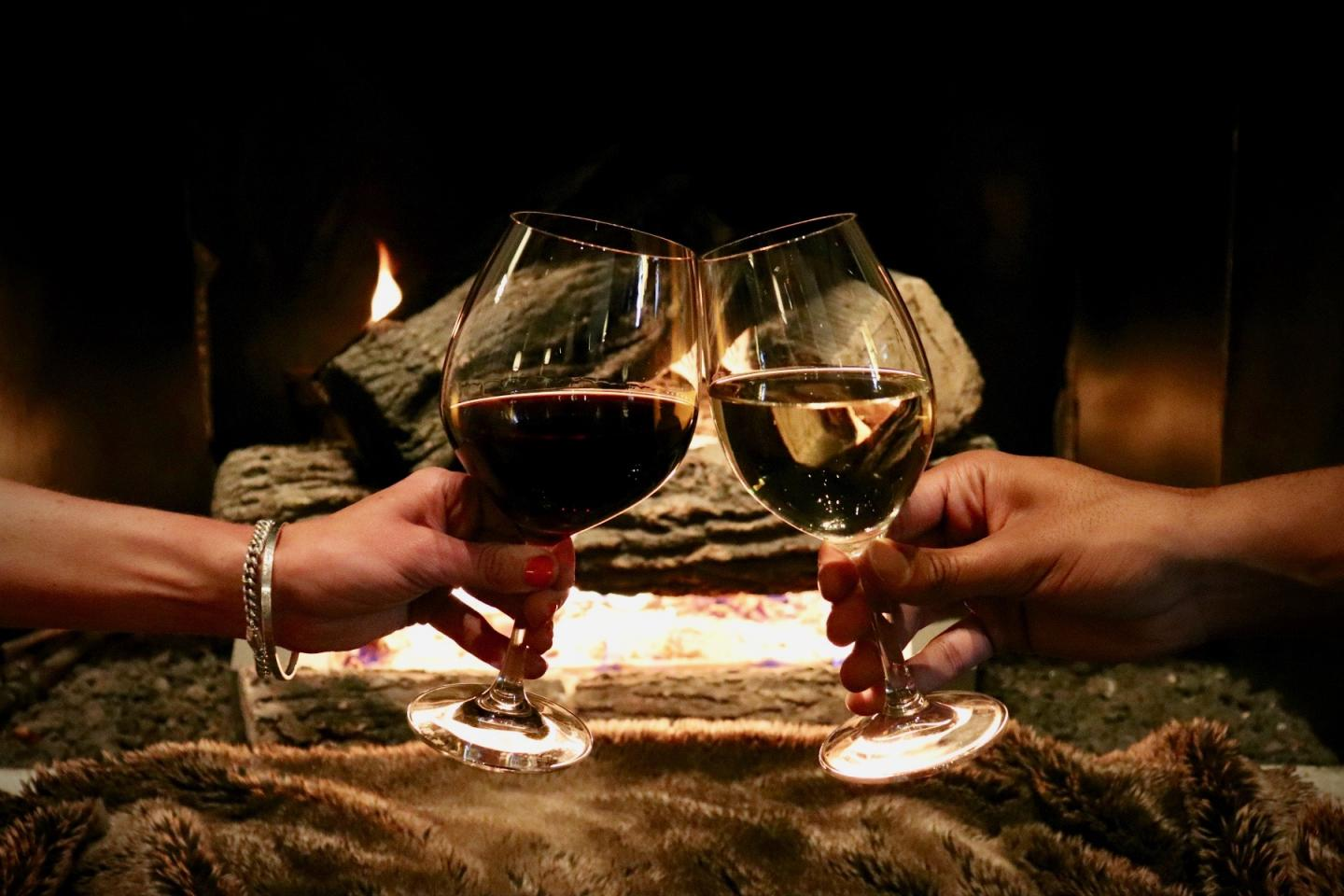 two glasses of wine cheersing in front of the fireplace at Booth One