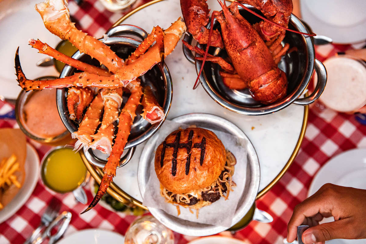 Crab Cellar burger, crab legs and lobster on a table